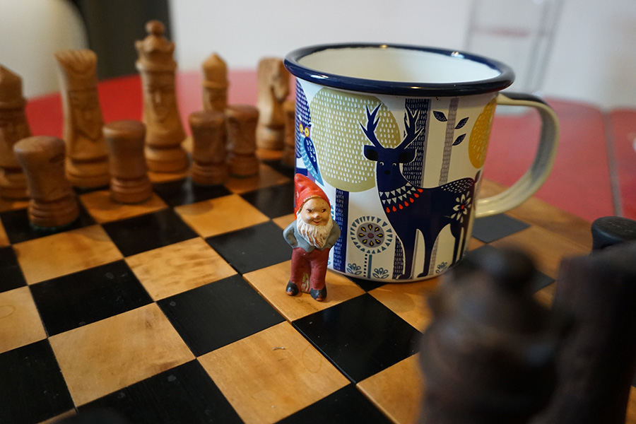 photo of a garden gnome on a chess set with a coffee cup with a deer drawing on it. British Columbia, Canada