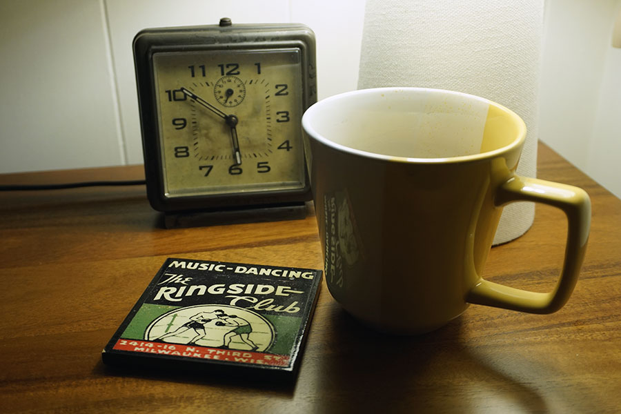 photo of coffee cup next to an old clock.